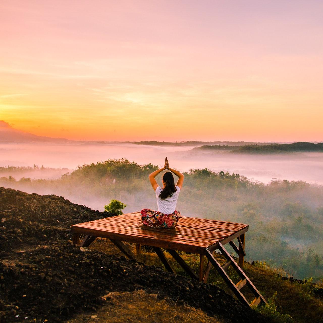 Meditierende Frau auf Plateau sitzend