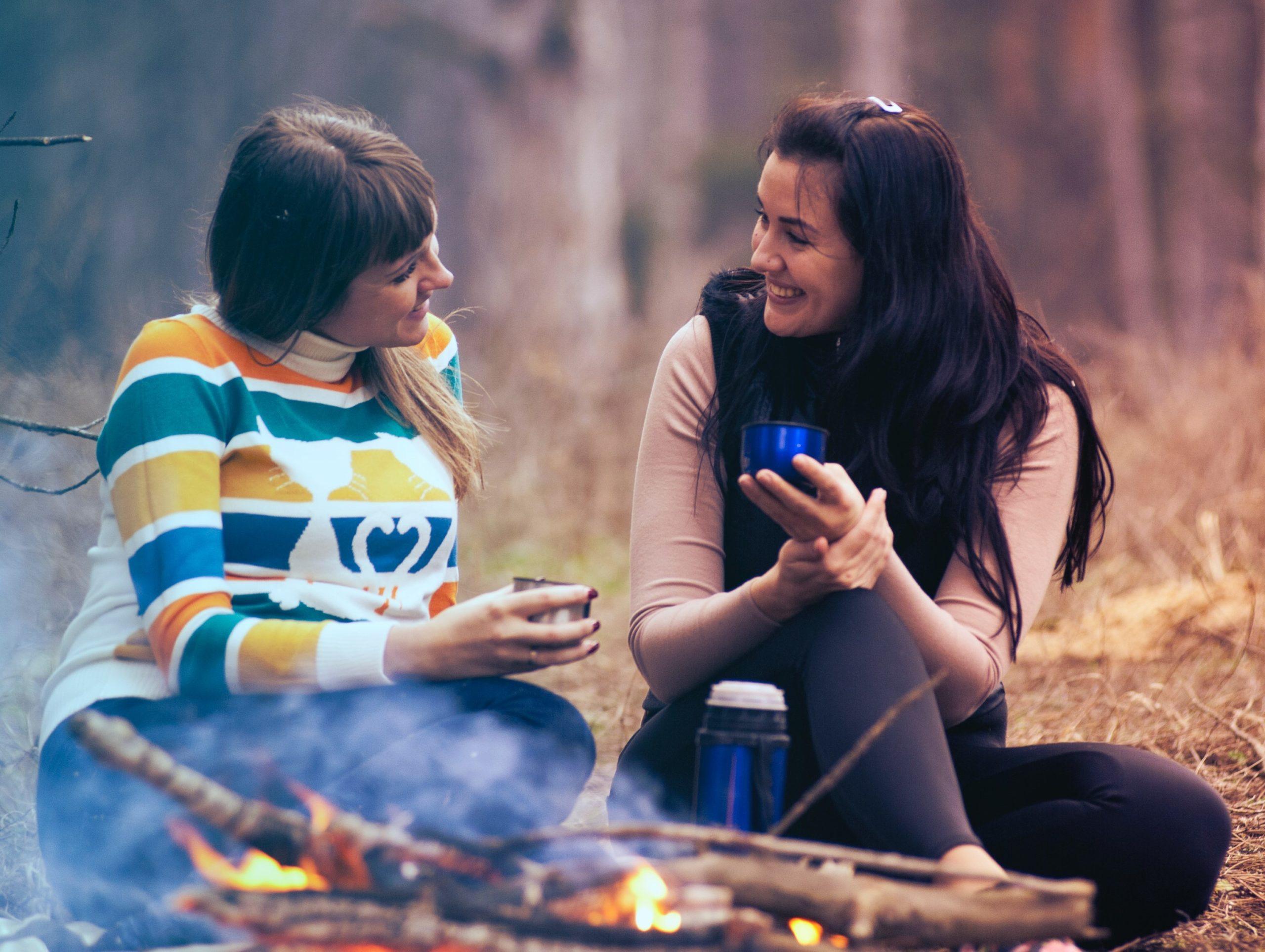 Zwei Frauen unterhalten sich sitzend am Lagerfeuer
