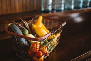 Einkaufskorb auf Tisch gefüllt mit Obst und Gemüse