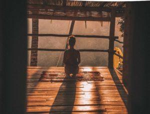 Frau sitzt auf Knien mit Rücken zugewandt und schaut in die Ferne