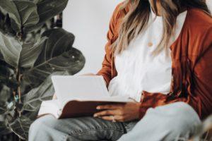 Frau sitzt mit Buch in der Hand